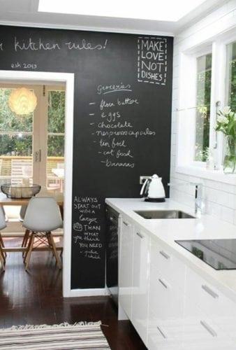 Cozinha pequena, ganhou uma super bossa com a parede de fundo em lousa a porta azul contrastando.. Cozinha branca e preto, o preto entrou com a parede em lousa.