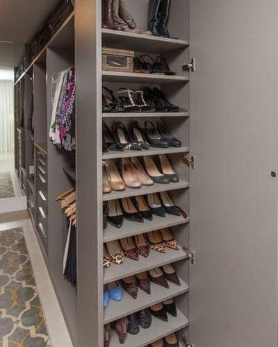 Arrumação dos sapatos. Lateral do armário com prateleiras finas,