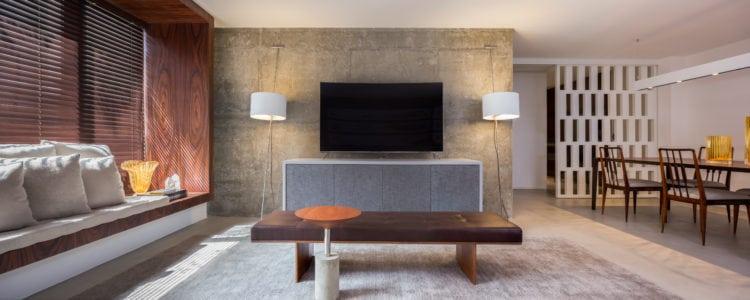 Apartamento pratico e sem excessos nos Jardins. Sala em tons neutros e parede em cimento.