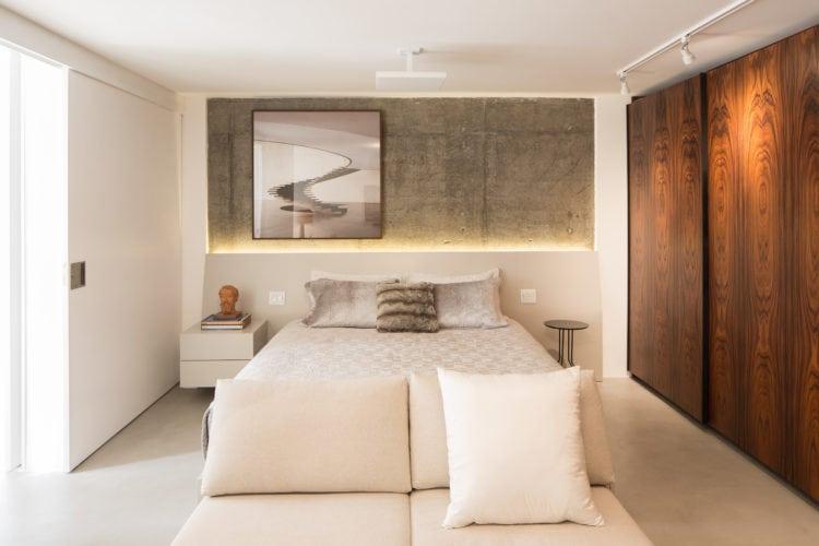 Apartamento pratico e sem excessos nos Jardins. Quarto de casal com parede de fundo da cama em cimento.