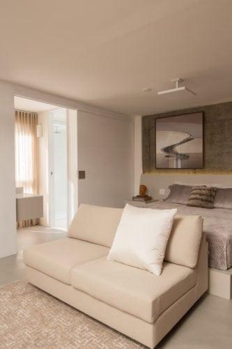 Apartamento pratico e sem excessos nos Jardins. Quarto de casal com parede de fundo em cimento.