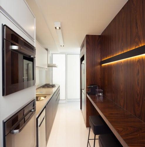 Apartamento pratico e sem excessos nos Jardins. Cozinha moderna com forno embutido e espaço para refeição forrada em madeira