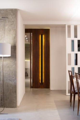 Apartamento pratico e sem excessos nos Jardins. Parede forrada em lamina de madeira e iluminação