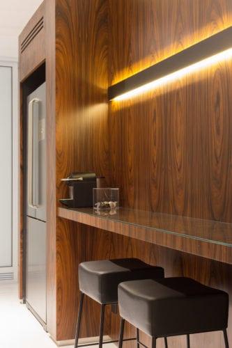 Apartamento pratico e sem excessos nos Jardins.. Cozinha contemporânea, espaço para bancada revestida em lamina de madeira.