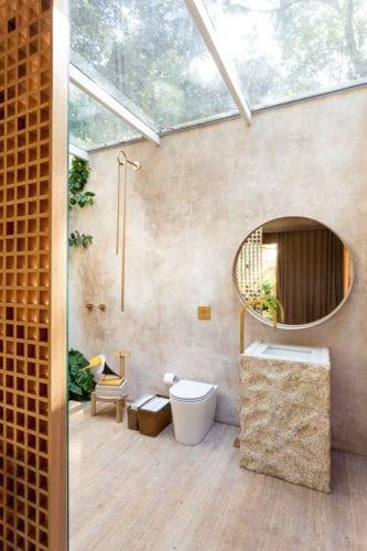 """""""Casa da Árvore"""" na mostra CASACOR SP 2018, Banheiro integrado a natureza , com teto de vidro e bancada em pedra sabão.pedra bruta e ausência de teto no box, concretizam nossa ideia de casa de banho ao ar livre."""