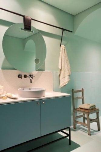 CASACOR SP: Ambiente Léo Shehtman, Casa dos arcos. Banheiro todo pintado em verde clarinho e espelho redondo na bancada.