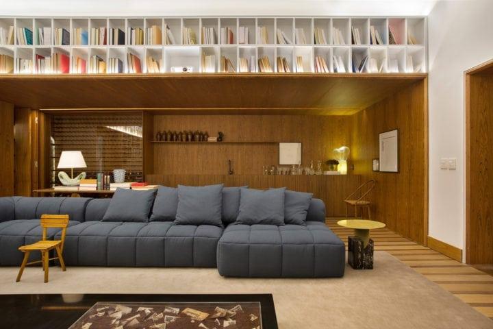 sofa e parede revestida de madeira de BC Arquitetos para casa cor sp
