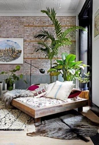 Decorando com os signos, a casa do Taurino. Sala com parede de tijolinho, plantas e sofá grande.