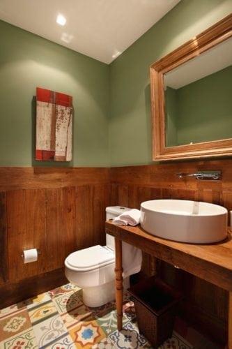 Decorando com os signos, a casa do Taurino. Lavabo com parede verde, ladrilho hidráulico no piso e lambri de madeira.