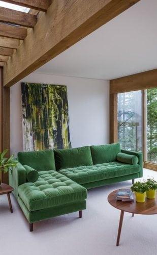 Decorando com os signos, a casa do Taurino. Sala com sofá verde e madeira no teto.