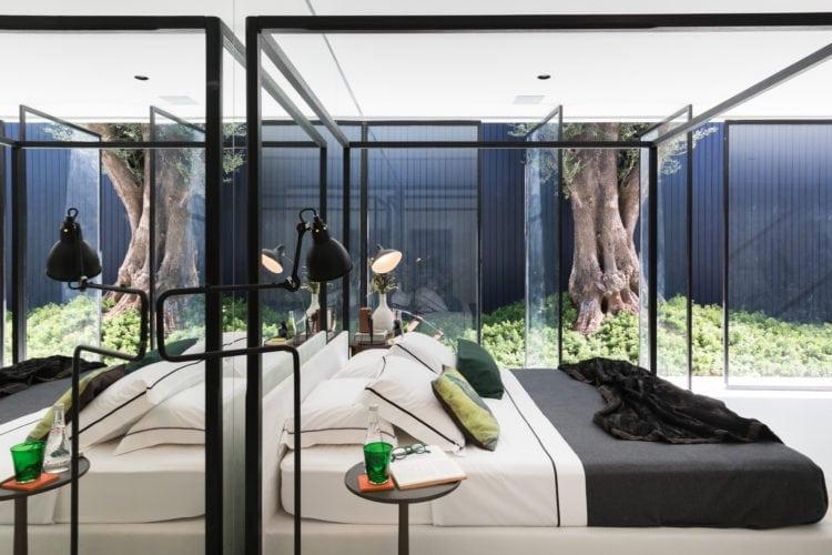 Espaço de João Armentano na Casa Cor SP 2018. Quarto com cama dossel em estrutura preta , com esquadrias abertas para o jardim.
