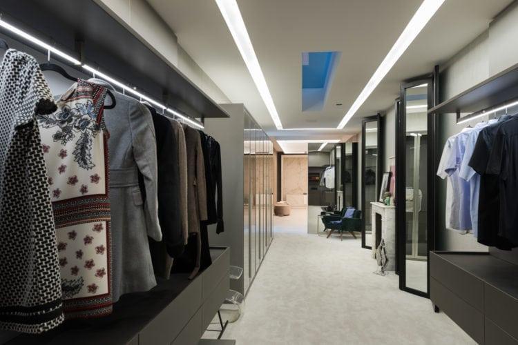Espaço de João Armentano na Casa Cor SP 2018. Closet com armários abertos, carpete no piso e aberto para o banheiro.