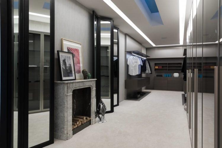 Espaço de João Armentano na Casa Cor SP 2018. Closet com lareira, armários abertos e carpete no piso.