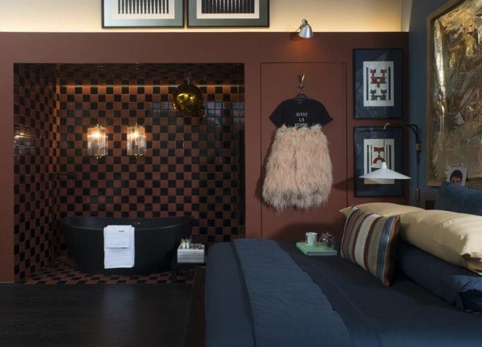 Michel Safatle apresenta Loft Eu, Tu e Elas na CasaCor SP. Nicho revestido com pastilhas marrons, abriga uma banheira preta. Integrada ao quarto.