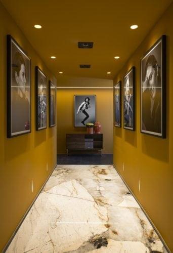 Michel Safatle apresenta Loft Eu, Tu e Elas na CasaCor SP. Corredor pintado na cor amarelo mostarda, com fotografias ma parede de autoria de Bob Wolfenson