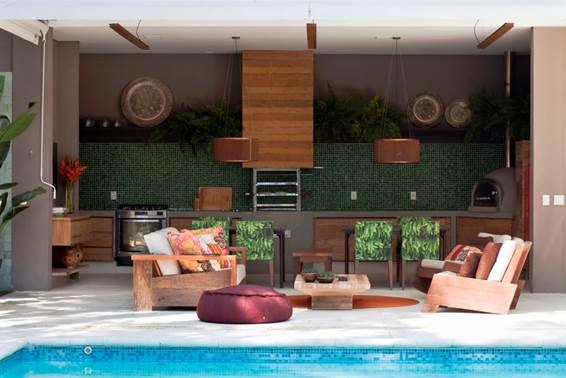 O clima descontraído do Rio de Janeiro, em uma casa em São Paulo de 720m2. Area da churrasqueira com poltronas de Carlos Motta .