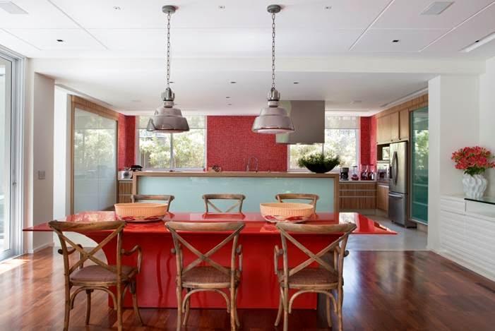 O clima descontraído do Rio de Janeiro, em uma casa em São Paulo de 720m2. Cozinha com pastillhas vermelhas e mesa tb vermelha.