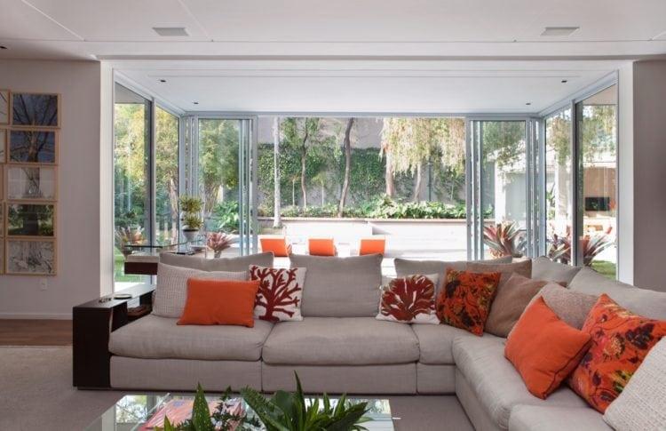 O clima descontraído do Rio de Janeiro, em uma casa em São Paulo de 720m2. Janelas da sala para o jardim de bromélias.