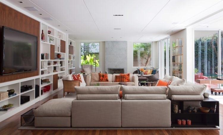 O clima descontraído do Rio de Janeiro, em uma casa em São Paulo de 720m2. Sala com tv e lareira ao fundo.