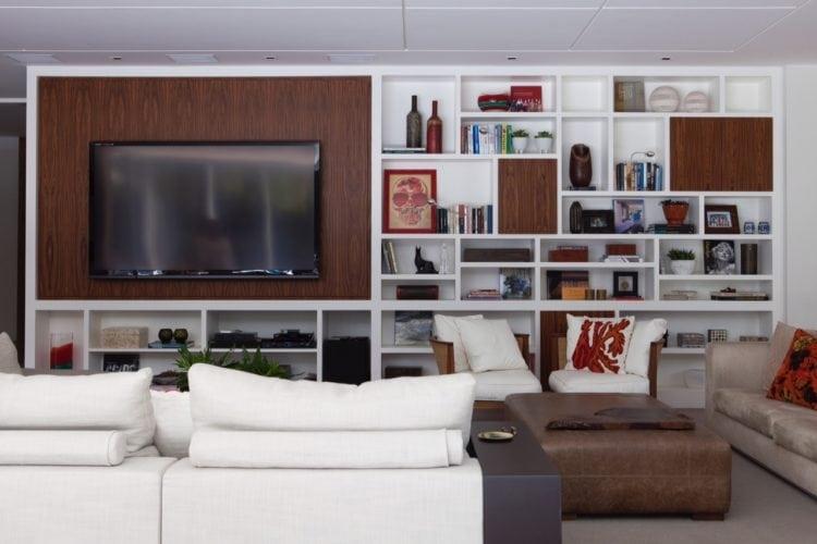 O clima descontraído do Rio de Janeiro, em uma casa em São Paulo de 720m2. Estante na sala com tv e livros.