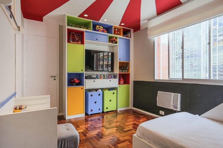 Decoração de quarto de criança, tem como inspiração, um Picadeiro. Faixas em vermelho e branco pintadas o teto, remetem ao céu do picadeiro. Marcenaria em tons vibrantes .