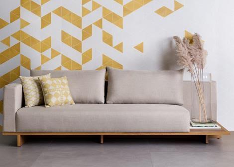 Obras de Candido Portinari foram inspiração para a criação de porcelanato. Salpicado em branco e amarelo na parede de fundo do sofá.
