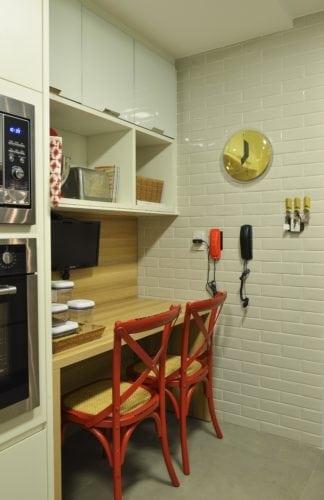 Cozinha com cadeiras vermelhas e parede de tijolinhos brancos do Apartamento no Le Parc Salvador, assinado por Manarelli Guimaraes e fotos de Marcelo Negromonte