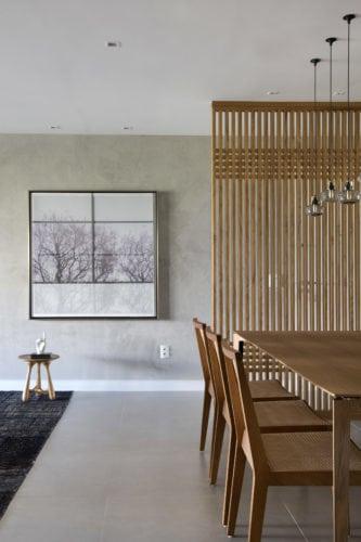 Sala de jantar com piso de porcelanato cinza e painel de madeira freijó vazado
