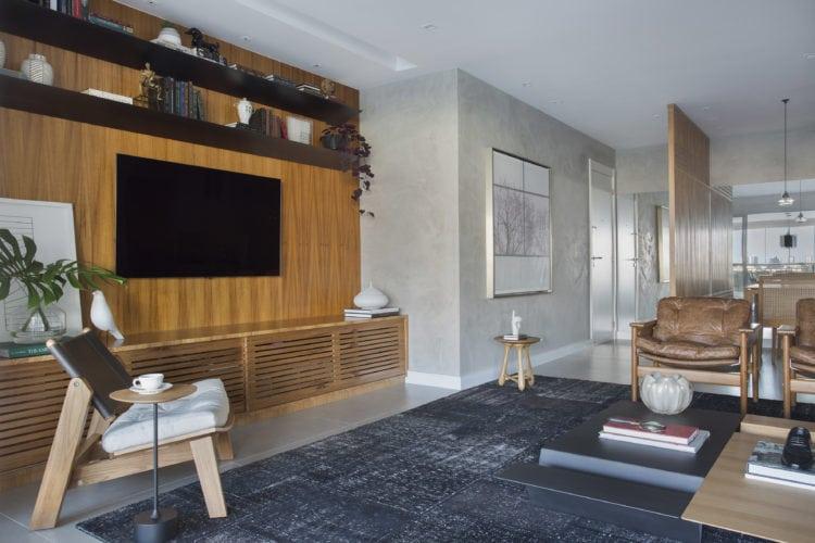 Sala com estante em madeira freijó para a tv, tapete preto .