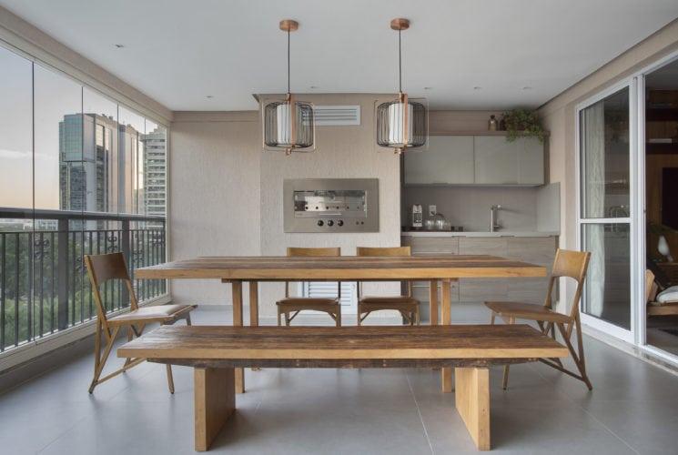 Varanda fechada com cortina de vidro, para abrigar uma churrasqueira, mesa e bancada.