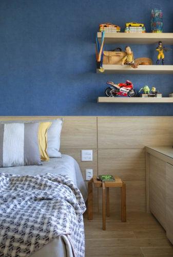 Quarto de criança, com parede pintada de azul e cabeceira em madeira ao longo da parede.
