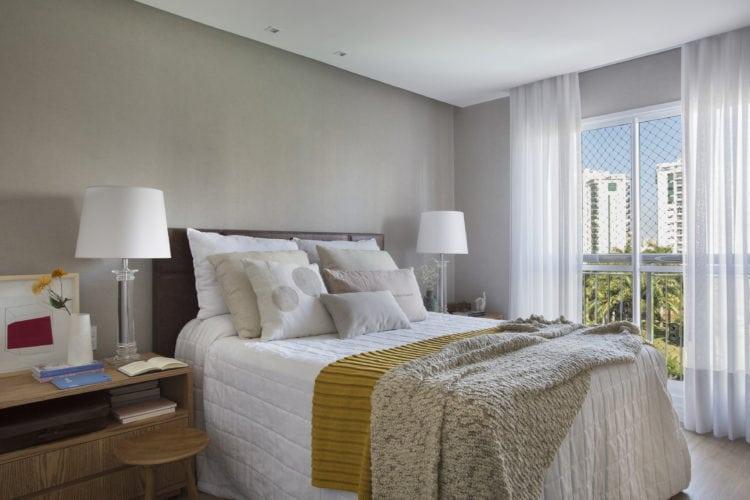 Quarto de casal com a parede de fundo da cama pintada de cinza.