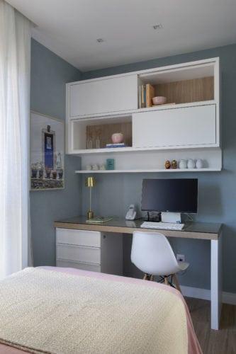 Bancada de estudos em frente a cama, com nichos brancos e bancada em madeira.