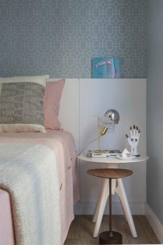 Quarto de menina com roupa de cama rosa e papel de parede azul.