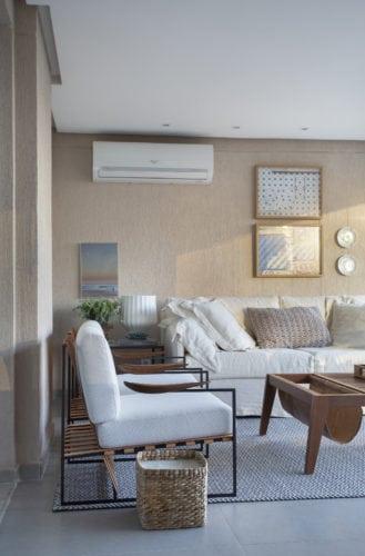 Varanda fechada com cortina de vidro, com ar condicionado e sofás brancos