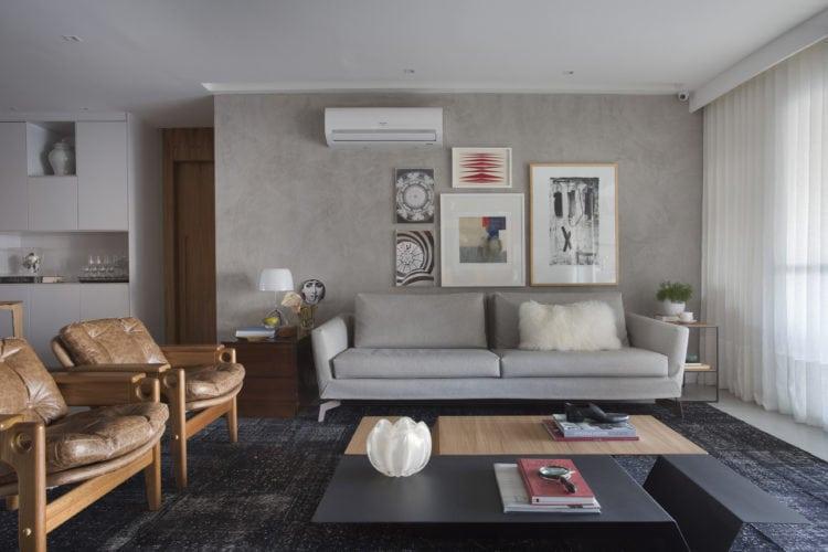 Sala com parede cinza em pintura especial, sofá em couro cinza e cadeiras do design Sergio Rodrigues