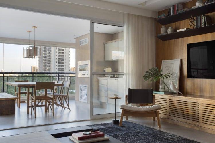 Sala com esquadria para a varanda com churrasqueira. Poltrona do design Fernando Mendes
