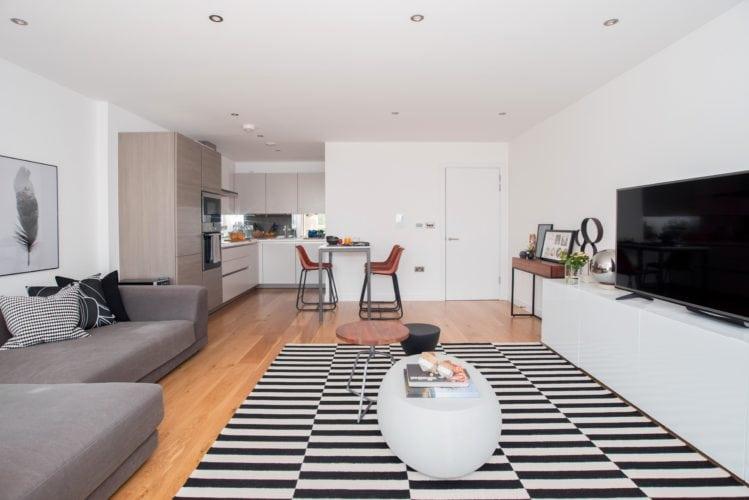 Arquitetas cariocas assinam o décor de apartamento em Londres. Sala ampla com tapete preto e branco.