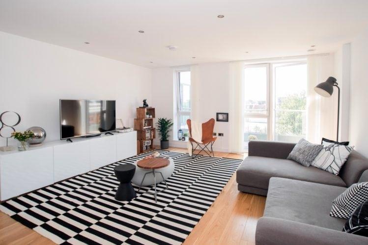 Arquitetas cariocas assinam o décor de apartamento em Londres. Sala ampla, com tapete preto e branco e sofá cinza.