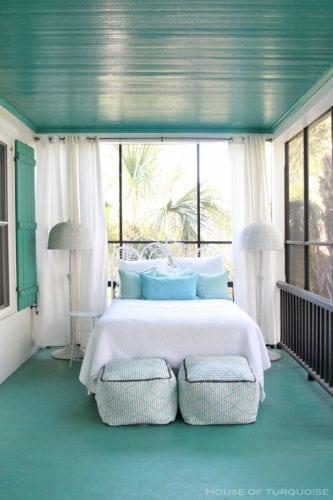 Cama embaixo da janela, quarto com janelas ao redor e o teto turquesa.