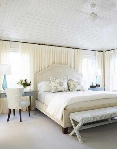 Cama embaixo da janela, cabeceira alta com cortina atras fechada.