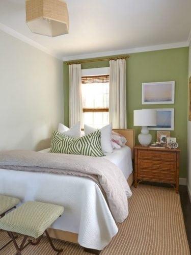 Cama embaixo da janela em um quarto pequeno , com parede verde e criado mudo ao lado da cama.