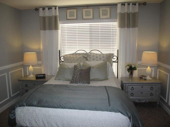 Cama embaixo da janela, nesse quarto com decoração clássica. Janela até o piso.