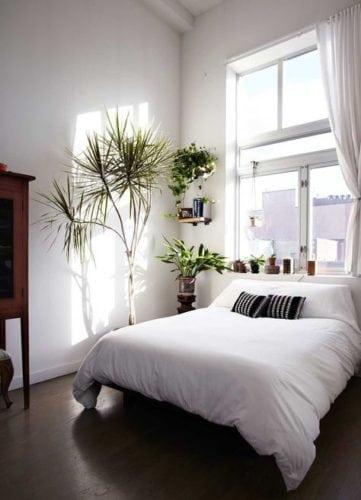 Cama embaixo da janela, que está dentro de um vão certinho para receber a cortina. Quarto com pé direito alto.