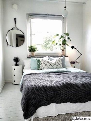 Cama embaixo da janela, com vasinho de planta .