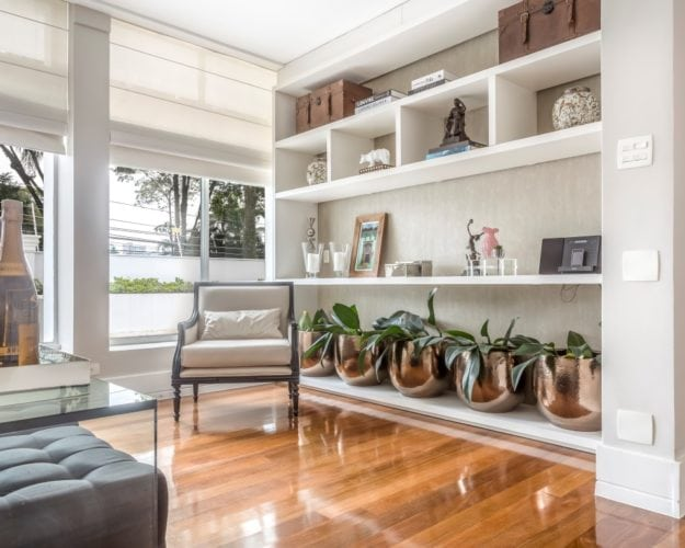 Sala de estar c estante branca e objetos de decoração da Contudo Décor assinada por Triarq Studio Arquitetura e foto de João Paulo