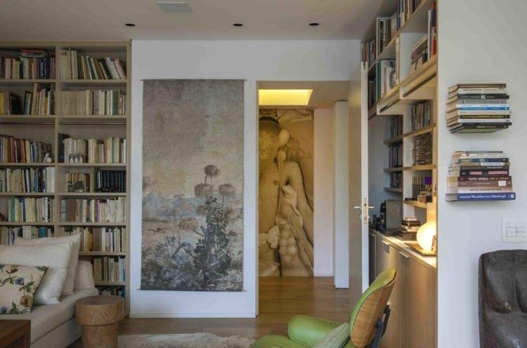 Estante de livros e gravura na parede no apto assinado por Tania Eustáquio