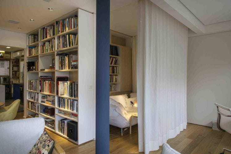 Estante de livros e pilar azul no apto assinado por Tania Eustáquio
