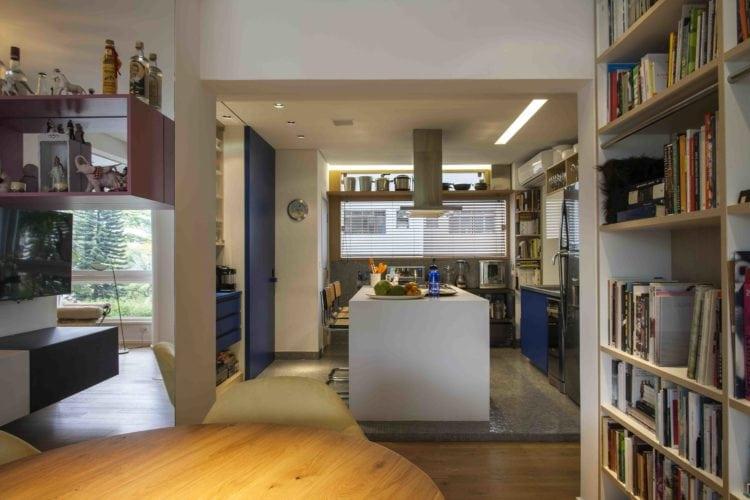 Estante de livros e mesa de jantar e cozinha no apto assinado por Tania Eustáquio