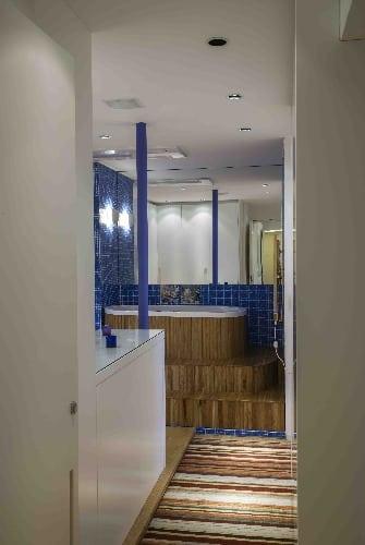 Banheiro e ofurô revestido de pastilhas azuis assinado por Tania Eustáquio